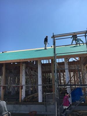 棟を上げる手伝いをする夫