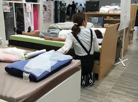 枕の計測をしてもらう夫