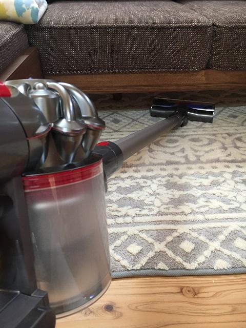 ソファーの下を掃除する掃除機
