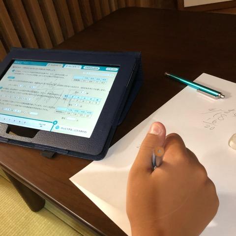紙と鉛筆を使って計算をする息子